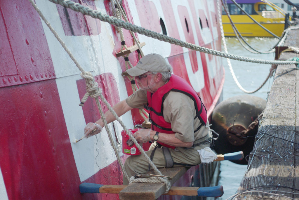 A volunteer painting lightship Ambrose exterior